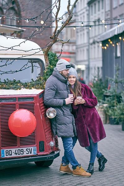 Pāris stāv pie Ziemassvētku rotājumiem klāta busiņa ar lampiņām un Rūdolfa sarkano degunu