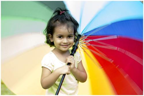 adorable baby girl with umbrella during mumbai monsoon