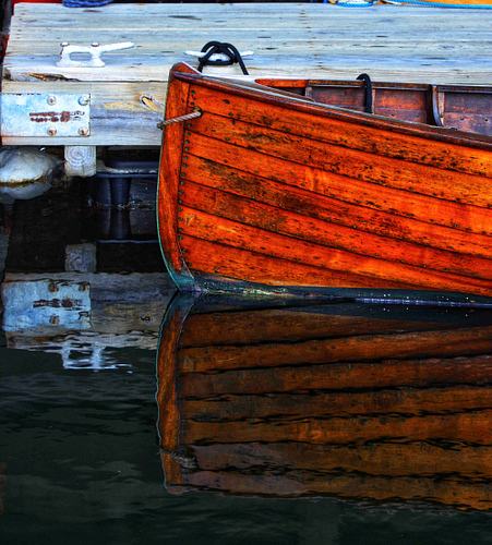 A wooden boat in Boston, side on with reflection