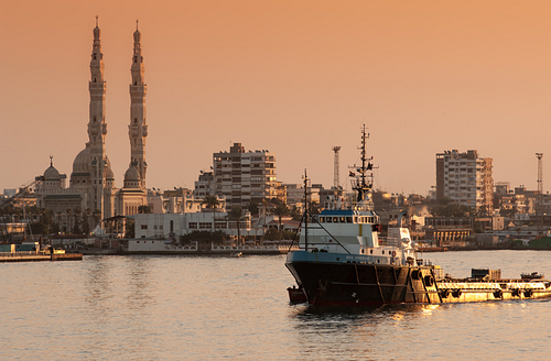 Tugboat passes mosque in Suez Canal