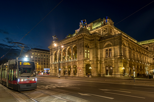 Wide shot of traffic passing the Vienna Opera House