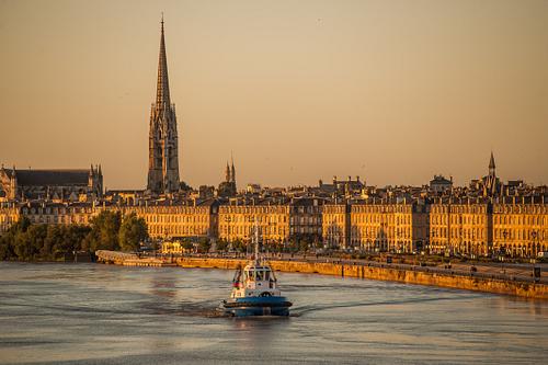 Tug boat sails up the Garonne river at dawn
