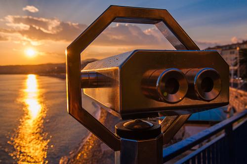 Tourist binoculars look over the setting sun in Nice