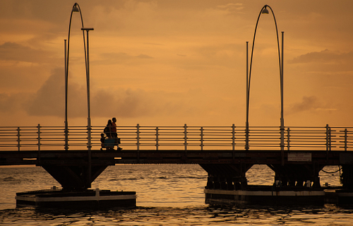 Family walk across bridge at sunset in Curacao