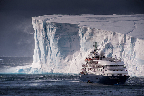 Cruise Ship In Front Of Huge Tabular Iceberg