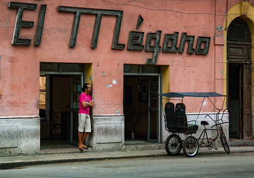 Man stands outside emptry store in Havana