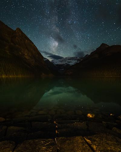 this is a picture of a lake and starry skies