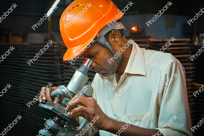 Man Inspecting in Microscope