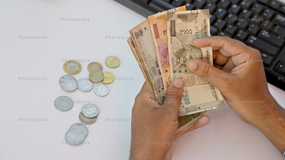 Man counting Indian rupee & coins
