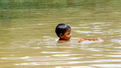 Small boy swimming in river