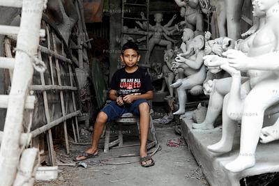 Boy sitting near durga