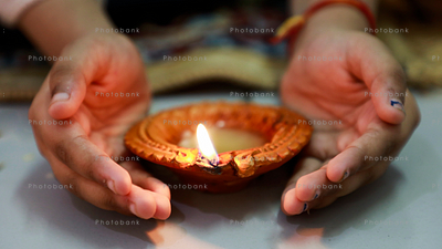 Little girl covering diya with hand