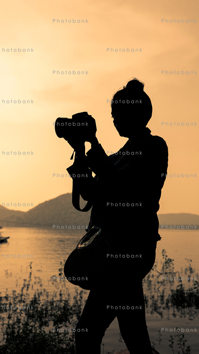 Silhouette of a woman clicking pictures