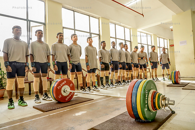 Group of boys preparing for weight lift inside gym