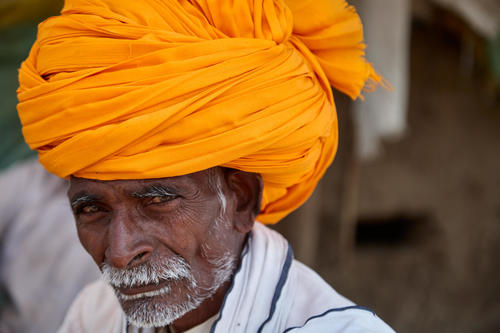 The turban, which is usually wound with a long piece of bright coloured fabric is a protection against the harsh sunlight and is also considered to be a  symbol of the man's dignity and prestige. This farmer had worn a brand new one since he was buying a plot of land that day and it is considered to be a very auspicious event.