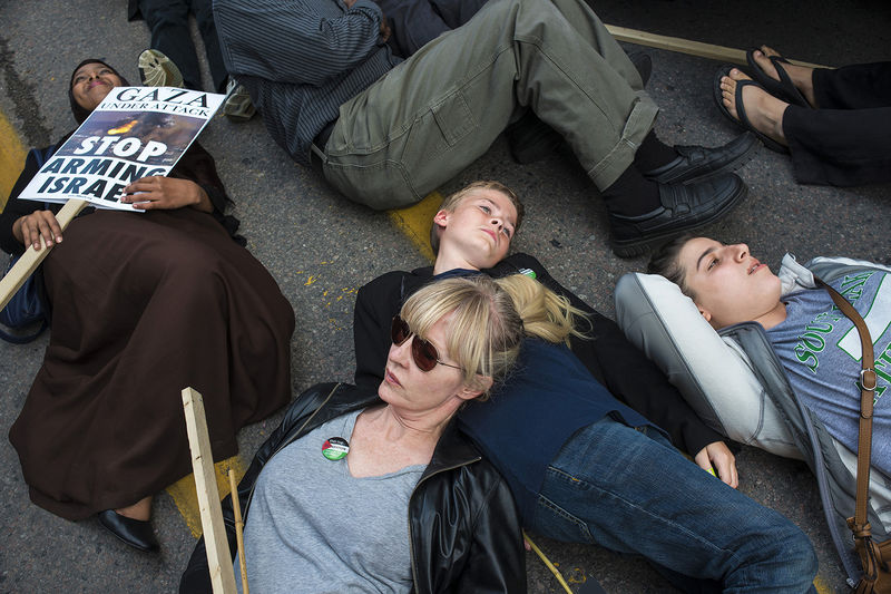 Protesters lay on the ground to remember the victims of the Israeli attacks on Gaza. Hundreds of people marched in downtown Toronto protesting the Israeli attacks, Toronto, July 30, 2014.