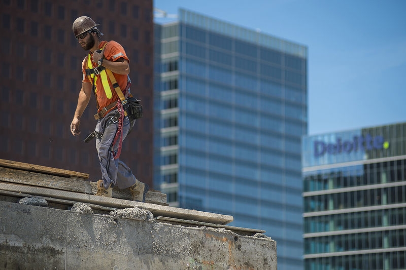 A construction worker walks along the unfinished floor of a condo development in downtown Toronto, on Thursday, June 30, 2016.