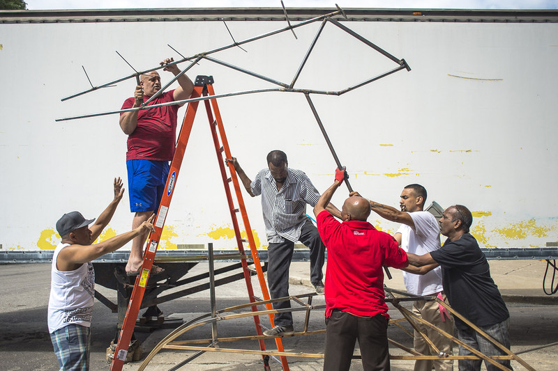 Curtis Eustace (top of ladder) and his team of builders assemble the structure that will hold one of the costumes of Mas-K Club. A Trinidad native, Eustace is considered a legend in the business and spends great part of the year traveling to participate in other carnivals.