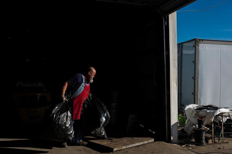 "Phil carries two plastic bags full of aluminum cans to be weighed. He doesn't have an assistant and does all the work around the recycling plant. ""There is a lot of competition these days and profits are not what they used to be,"" he says."