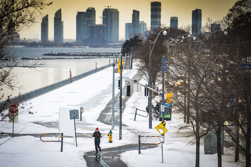 A jogger is seen running along Lake Shore West after a snowfall, Toronto, December 22, 2017.