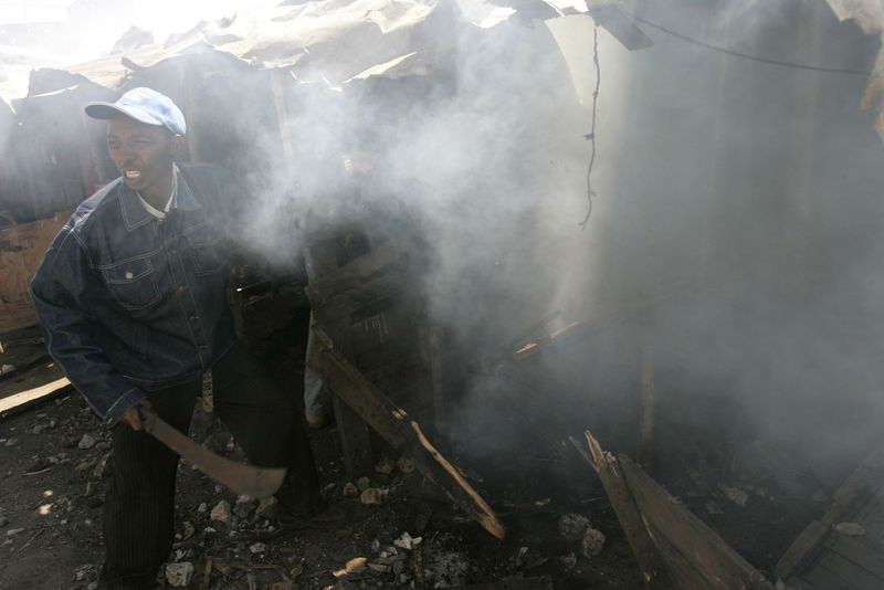 A protestor run past burning buildings, Wednesday, Jan. 2, 2008 during riots in the Mathare slum in Nairobi.