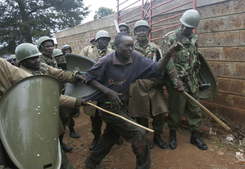 Police beat an opposition supporter, Monday, Dec.31, 2007 during riots in the Kibera slum in Nairobi
