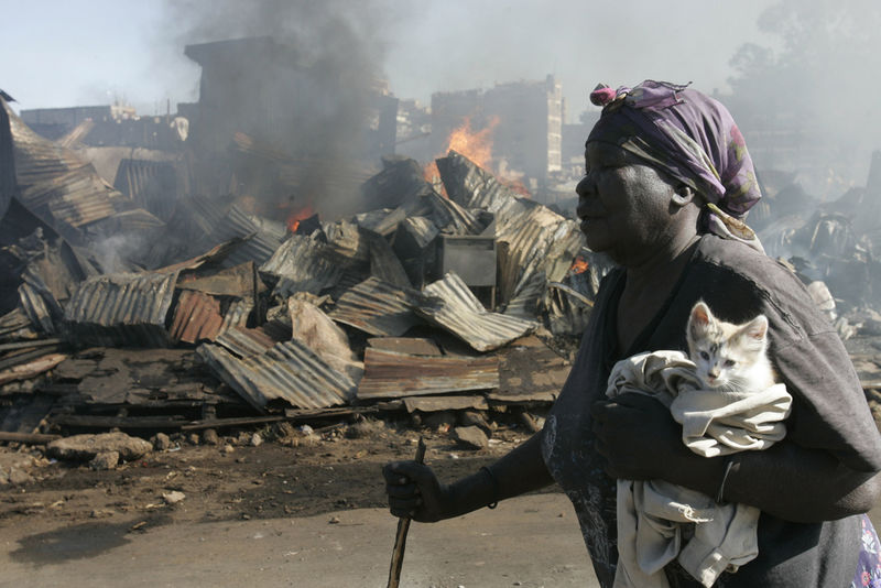 An old woman carry a kitten she saved from her shop after it was burned down, Sunday, Dec.30, 2007 during riots in the Mathare slum in Nairobi.