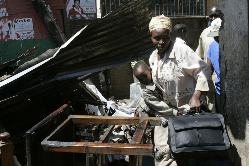A woman and her child is escorted by plainclothes policemen, unseen, Wednesday, Jan. 2, 2008 during riots in the Mathare slum in Nairobi.