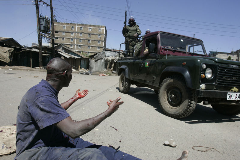 A man that was attacked with machetes plead for help, Wednesday, Jan. 2, 2008 during riots in the Mathare slum in Nairobi.