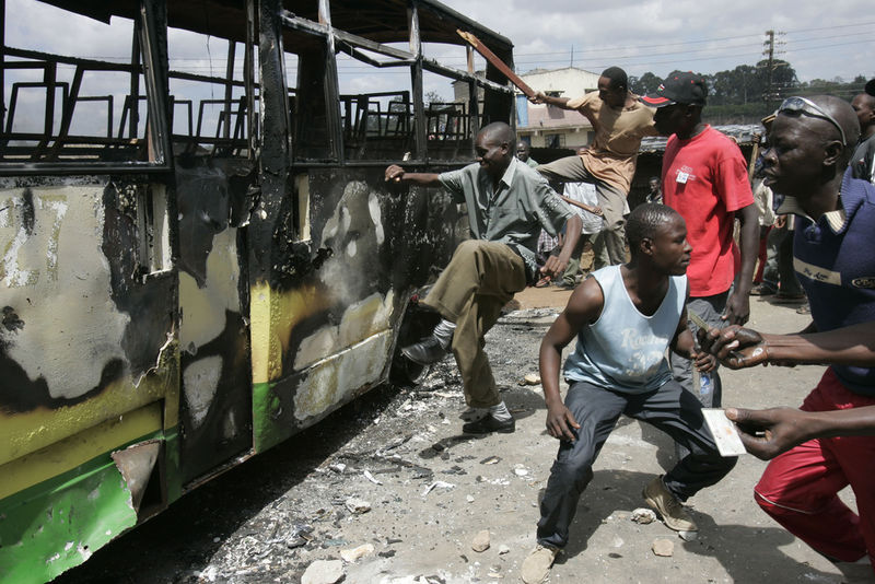 Orange Democratic movment supporters attack a bus that they burned, Sunday,Dec. 30, 2007 during riots in the Mathare slum in Nairobi