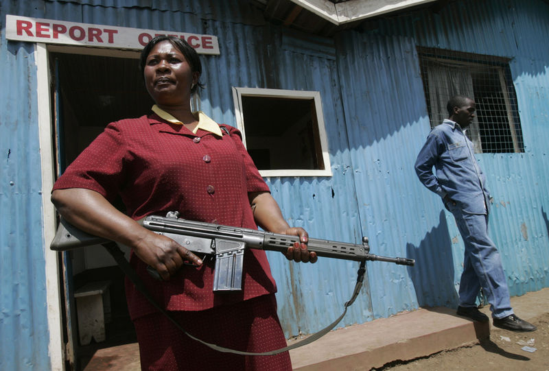 A woman from the administration police stand ready with an assault rifle as members from a feared Kikuyu criminal gang, the Mungiki , arrive at a Red Cross food distibution point to protect people recieving food aid, Thursday, Jan. 10, 2008 in the Kibera slum in Nairobi.
