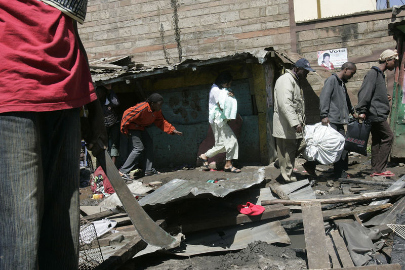 People flee as a protestor hold a machete , Wednesday, Jan. 2, 2008 during riots in the Mathare slum in Nairobi.