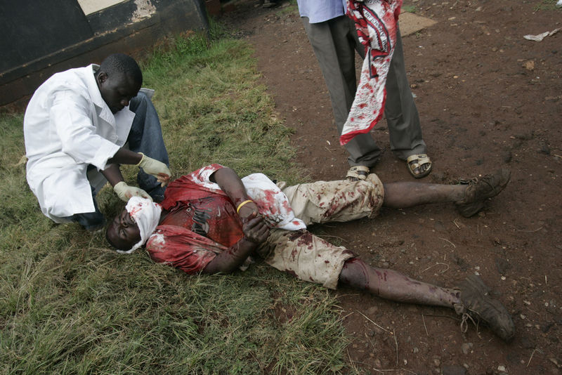 A nurse assist a man that collapsed outside a small clinic after he was shot in the face, Friday, Jan. 18, 2008 during clashes between the police and opposition supporters in the Kibera slum in Nairobi