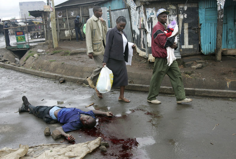 People walk past the body of a man killed, Sunday, Jan. 20, 2008 during ethnic fighting in the Mathare slum in Nairobi.