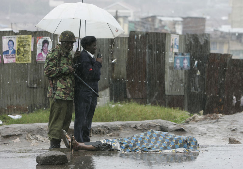 Police stand next to the body of a man that was attacked with machetes and killed by unknown attackers, Friday, Jan. 18, 2008 in the Mathare slum in Nairobi.
