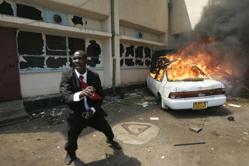 An opposition supporter react after they set a car and building on fire, Wednesday, Jan. 23, 2008 in Nairobi, Kenya.
