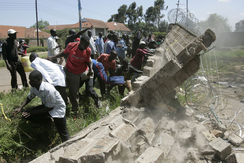 Opposition supporters break down a wall, Wednesday, Jan. 23, 2008 in Nairobi, Kenya.