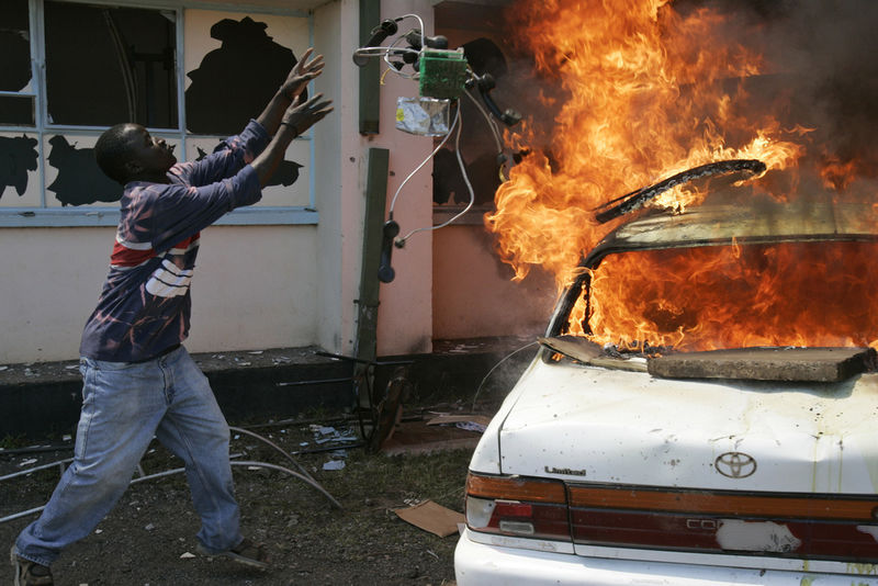 An opposition supporter throw old telephones into a car that was set ablaze, Wednesday, Jan. 23, 2008 in Nairobi, Kenya