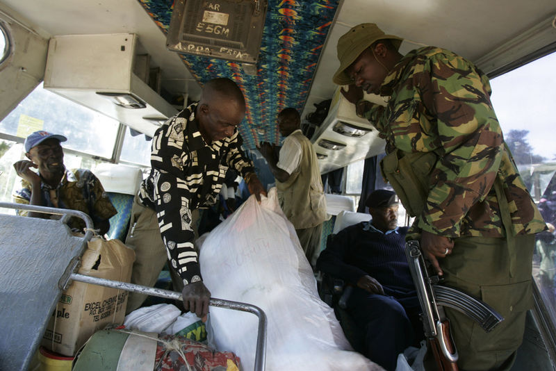 Kenyan policemen look on as displaced people board a bus with their belongings, Sunday, Feb. 3, 2008 as they are transported in buses under armed guard from a police station where they took shelter in Limuru near Nairobi to their home areas in western Kenya.