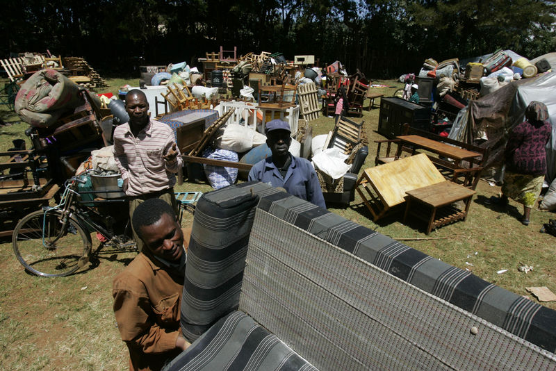Displaced people put their belongings on a bus, Sunday, Feb. 3, 2008 as they are transported in buses under police guard from a police station where they took shelter in Limuru near Nairobi to their home areas in western Kenya.
