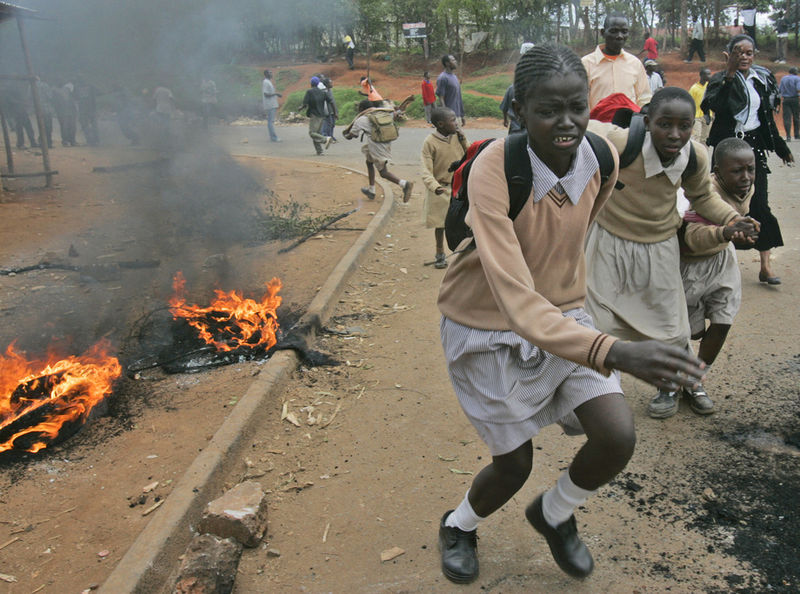 School children run to saftey past burning barricades, Tuesday, April 8, 2008 during clashes between police and opposition party supporters in the Kibera slum in Nairobi