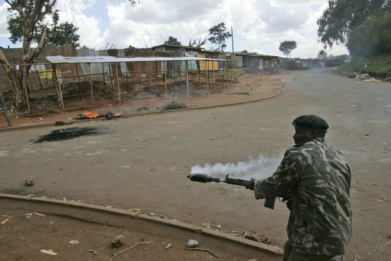 A Kenyan policeman prepare to fire tear gas , Tuesday, April 8, 2008 during clashes between police and opposition party supporters in the Kibera slum in Nairobi.