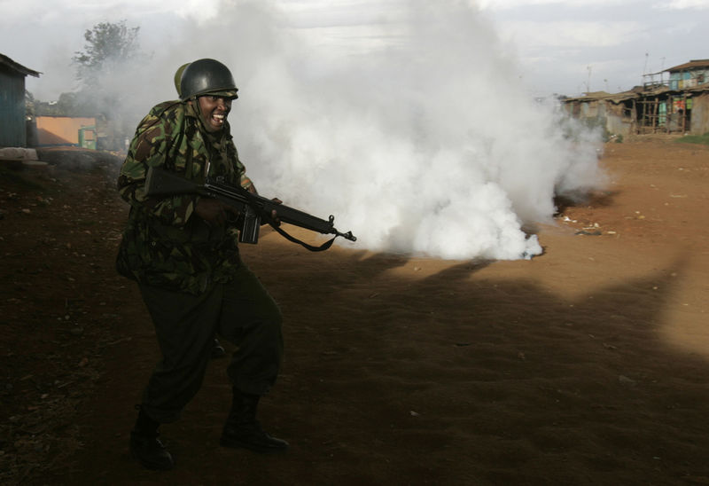 Police react as protesters throw back tear gas fired by the police, Wednesday, April 9, 2008 during clashes between police and opposition party supporters in the Kibera slum in Nairobi