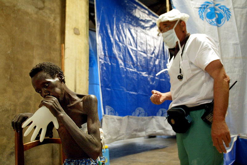 A Congolese man breath into a latex glove while a doctor looks on at an Medecins Sans Frontieres hospital, Monday, June 2. 2003 after he was shot through his chest injuring his lung during an attack by tribal fighters three weeks ago in Bunia.