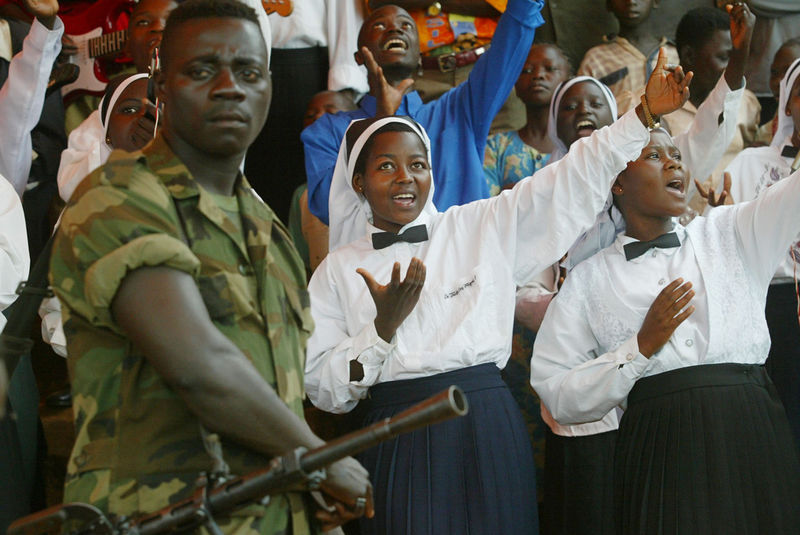 A fighter of the rebel Union of Congolese Patriots, UPC, stand in front of a choir group during a rally held by the leader of the UPC Thomas Lubanga , Thursday, June 5. 2003 in Iga Barriere some 25 kilometers outside Bunia, Congo