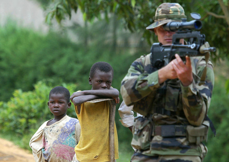 A Congolese boy look at a French soldier looking through the scope of his rifle, Wednesday, June 11. 2003 at a French army checkpoint in Bunia, Congo.