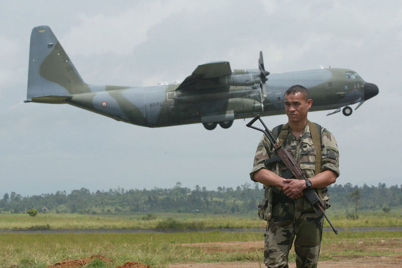 A French soldier stand guard at Bunia airport ,Tuesday, June 10. 2003 as a French military cargo plane take off after it have dropped of some of the first French combat troops leading an international force to be deployed in Bunia .