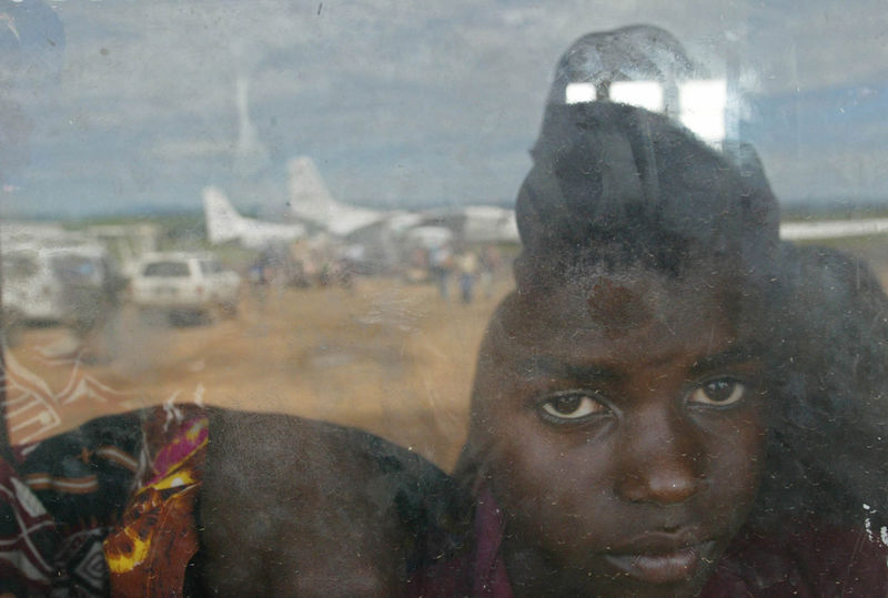 A Congolese child wait to be evacuated at Bunia airport while UN planes can be seen in the reflection of a window, Friday, May 16. 2003 in the Congo.