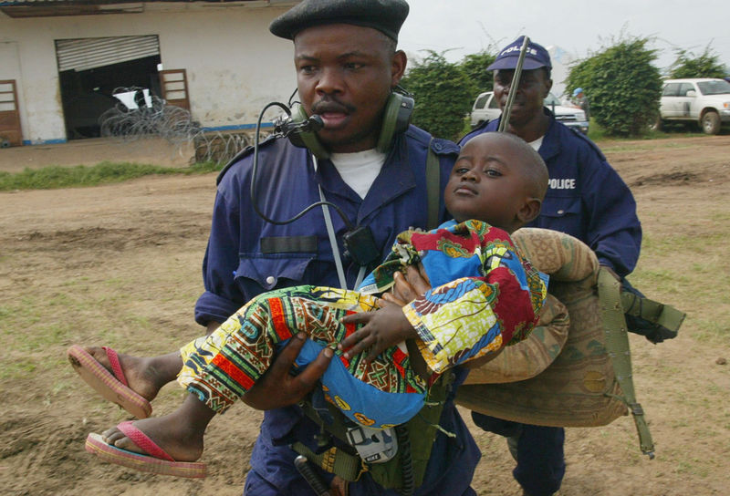 A Congolese policeman runs with a child to a waiting aircraft at Bunia airport, Friday, June 20, 2003 as a few internally displaced people are evacuated from Bunia.