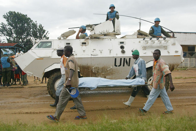 Red Cross volunteers carry the body of seventy year old Samuel Unega past United Nations troops from Uruguay as they remove him from hospital after he died, Saturday, May 31. 2003  from machete wounds inflicted on his skull by tribal fighters three weeks ago in Bunia, Congo.